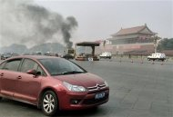 Vehicles travel along Chang'an Avenue as smoke raises in front of a portrait of late Chinese Chairman Mao Zedong at Tiananmen Square in Beijing October 28, 2013.REUTERS/Staff