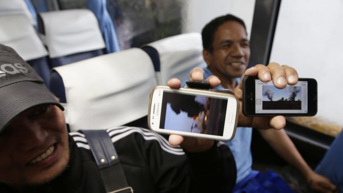 Overseas Filipino Workers (OFWs) Wency Ledesma and Ariel Nogol, left, show the photos taken with their cellphones, of the war-torn Benghazi in Libya upon arrival at the Ninoy Aquino International Airport following their repatriation Monday Aug. 4, 2014 at suburban Pasay city, south of Manila, Philippines. The Foreign Affairs Department and Overseas Workers Welfare Administration said about 13,000 Filipino workers are currently in Libya and less than a thousand has so far been repatriated. (AP Photo/Bullit Marquez)