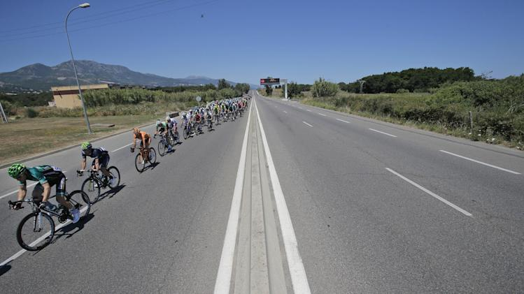 The pack rides on the left side of the road during the second stage of the Tour de France cycling race over 156 kilometers (97.5 miles) with start in Bastia and finish in Ajaccio, Corsica island, France, Sunday June 30, 2013. (AP Photo/Christophe Ena)