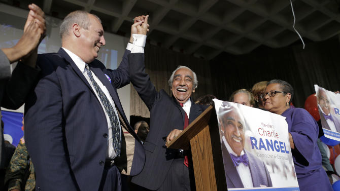 Rep. Charles Rangel, D-N.Y., center, raises his arms with Adam Clinton Powell IV, left, as he claims victory over opponent state Sen. Adriano Espaillat during a primary election night gathering, Tuesday, June 24, 2014, in New York. Rangel is seeking his 23rd term in Congress. Election officials told The Associated Press Tuesday night that the Democratic primary between Rep. Charles Rangel and state Sen. Adriano Espaillat in New York's 13th congressional district remains too close to call, with an undetermined number of absentee and provisional ballots outstanding. (AP Photo/Julie Jacobson)