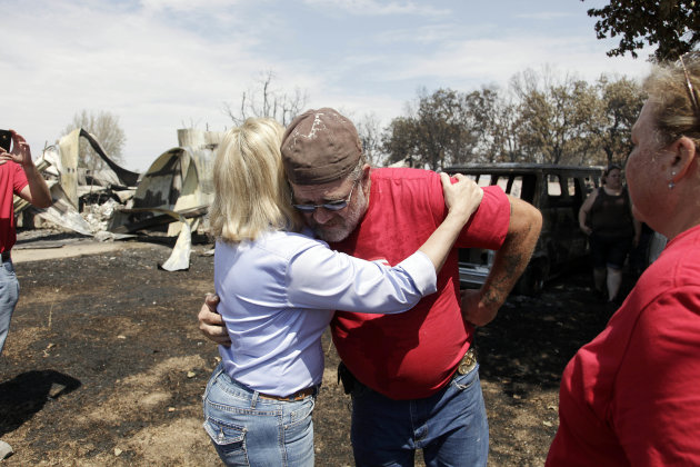 Gov. Mary Fallin, left, hugs James Sparr who lost his home and busines, in the background, after wildfires burned across the state in Mannford, Okla., Sunday, Aug. 5, 2012. (AP Photo/Tulsa World, Mike Simons)
