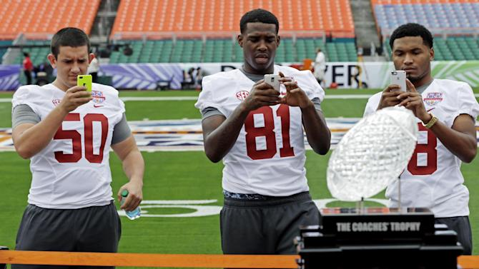 Alabama's Alphonse Taylor (50), Danny Woodson (81) and Josh Magee take pictures of The Coaches' Trophy during Media Day for the BCS National Championship college football game Saturday, Jan. 5, 2013, in Miami. Alabama faces Notre Dame in Monday's championship game. (AP Photo/David J. Phillip)