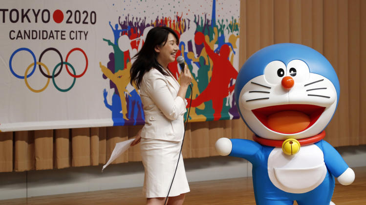 "FILE - In this Aug. 23, 2013 file photo, Doraemon, one of the most popular animation characters in Japan, participates in a kick-off ceremony of the Tokyo's bid to host the 2020 Olympics in Tokyo when Tokyo is bidding against Istanbul and Madrid to host the 2020 Olympics. Characters are not just for kids in Japan, but a part of business and social life. Some see Japan's cute-craze, known as ""kawaii,"" as a sign of immaturity, but others say it's rooted in a harmony-centered way of life that goes back to ancient animist traditions. Hello Kitty and Doraemon now face hordes of newcomers, many launched by municipal governments to promote tourism and local products. (AP Photo/Koji Sasahara, File)"