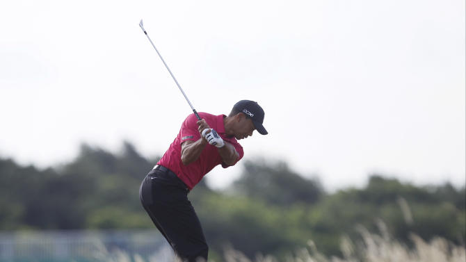 Tiger Woods of the US plays a shot on the 7th fairway during a practice round for the British Open Golf Championship at Muirfield, Scotland, Tuesday July 16, 2013. (AP Photo/Alastair Grant)