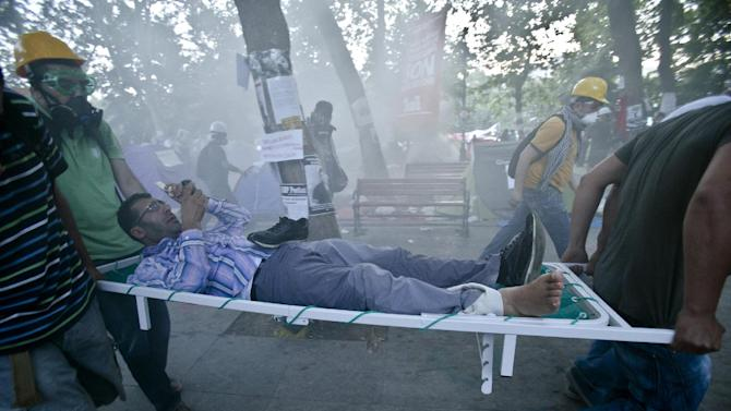 A man is evacuated on a stretcher after riot police flooded the Gazi Park with tear gas during clashes at the Taksim Square in Istanbul Tuesday, June 11, 2013. Riot police are re-entering Istanbul's Taksim Square after defiant protesters swarmed back in by the thousands. Massive plumes of tear gas billowed upward, and police fired water cannons Tuesday night. (AP Photo/Vadim Ghirda)