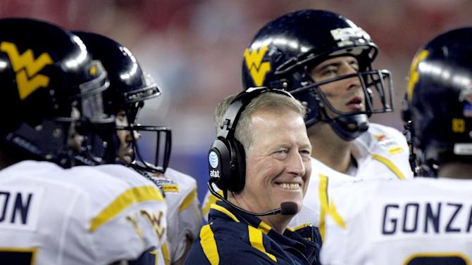 FILE - In this Jan. 2, 2008, file photo, West Virginia interim head coach Bill Stewart looks on from the sideline in the first half of the Fiesta Bowl college football game against Oklahoma in Glendale, Ariz. The former coach died Monday, May 21, 2012, of what athletic department officials said was an apparent heart attack. A statement issued by spokesman Michael Fragale said Stewart's family notified the university on Monday. Fragale said Stewart was golfing at the time. Stewart, 59, resigned last summer and was replaced by Dana Holgorsen the same night. Stewart had gone 28-12 in three seasons after taking over for Rich Rodriguez but failed to earn a Bowl Championship Series berth. (AP Photo/Paul Connors, file)