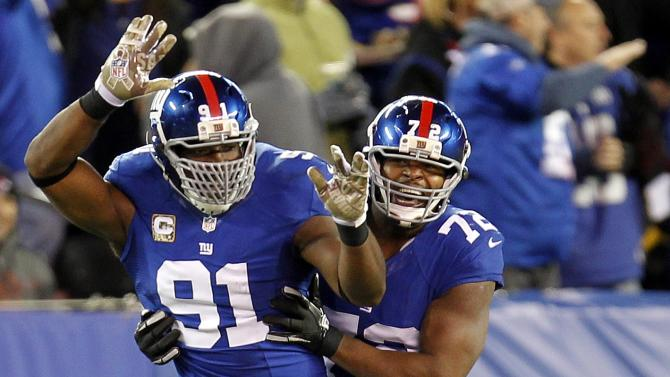 New York Giants defensive end Justin Tuck (91) and Osi Umenyiora (72) celebrate a fumble returned for a touchdown by Michael Boley during the first half of an NFL football game against the Pittsburgh Steelers, Sunday, Nov. 4, 2012, in East Rutherford, N.J. (AP Photo/Julio Cortez)