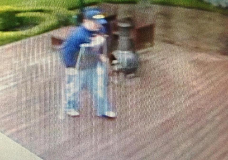 This image made from surveillance camera video provided by the Oakland County Sheriff's Office shows an attempted burglary suspect in crutches walking towards the house of musician Kid Rock in Clarkston, Mich. (AP Photo/Oakland County Sheriff's Office)