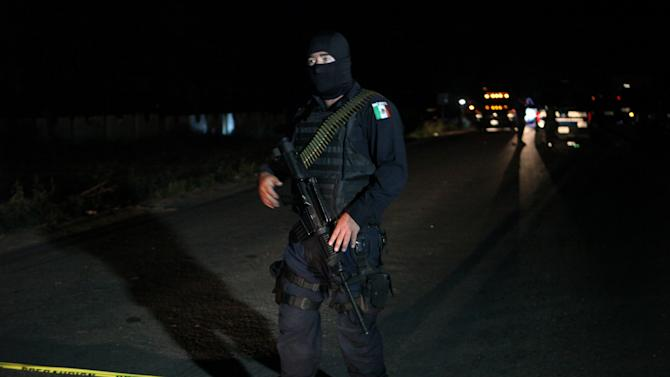 A federal police stands guard on a road after a shootout occurred in the town of La Ruana, Michoacan state
