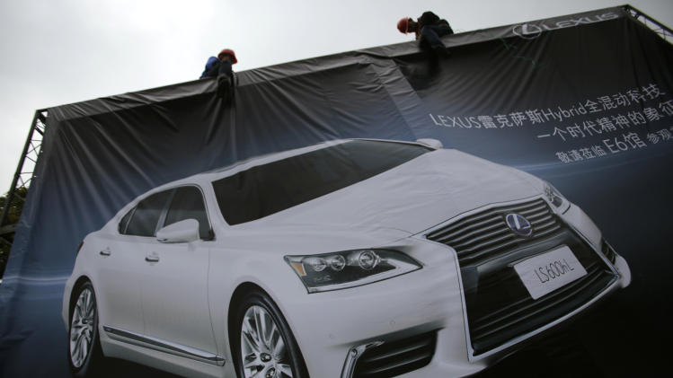 Workers hang an advertisement for a Lexus brand vehicle near the venue of the Shanghai International Automobile Industry Exhibition (AUTO Shanghai) at the Shanghai International Exhibition Center in Shanghai, China Thursday, April 18, 2013.  These should be good times for Chinese automakers as they prepare to show off their latest models at the Shanghai auto show. Their home market is the world's biggest and growing. But independent automakers such as Chery and Geely are being squeezed by bigger, richer global rivals including General Motors and Nissan that are creating low-priced models for local tastes. Domestic brands account for less than half of their own market.  (AP Photo/Eugene Hoshiko)