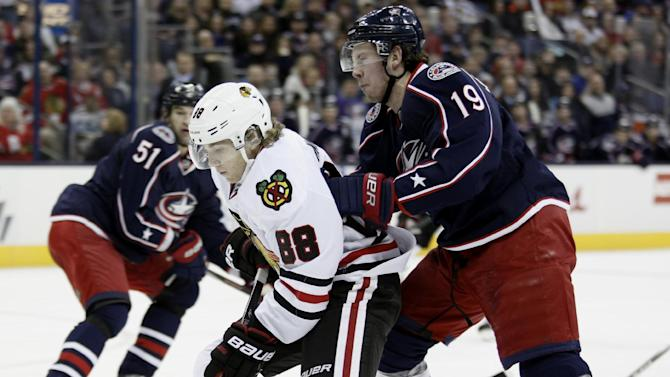 Chicago Blackhawks' Patrick Kane, left, works for the puck against Columbus Blue Jackets' Ryan Johansen  in the first period of an NHL hockey game in Columbus, Ohio, Saturday, Jan. 26, 2013. (AP Photo/Paul Vernon)