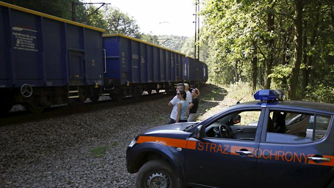 A railway security guards' car is seen next to people observing a cargo train travelling in an area where a Nazi train is believed to be at, in Walbrzych