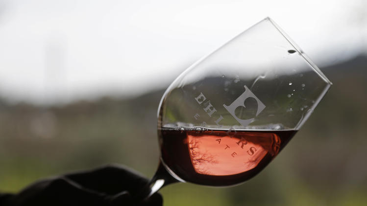 In this photo taken Monday, Jan. 7, 2013 winemaker Kevin Morrisey looks over a sample of Rose from a barrel at Ehler's Estate in St. Helena, Calif.  Proceeds from the winery's sales go to the Leducq Foundation which continues to award over $30 million annually to directly support international cardiovascular research. (AP Photo/Eric Risberg)