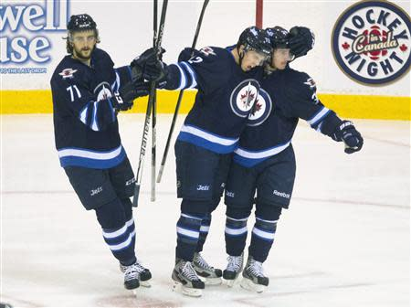 Winnipeg Jets Scott Kosmachuk celebrates with team mates Nic Petan and Julian Melchiori after he scored against the Washington Capitals in Belleville