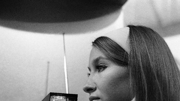 FILE - In a Sept. 1, 1966 file photo, a model looks at the Sinclair Micro vision set, a pocket size television set designed by Clive Sinclair that can go anywhere and claims to be the world's smallest TV, at Earls Court, London. The rectangular face plate of the cathode tube has a diagonal measurement of two inches. It's been nearly a quarter of a century since the last big jump in battery technology, which led to the lithium ion. As 21st century technology strains to be ever faster, cleaner and cheaper, the battery, an invention from more than 200 years ago keeps holding it back.  (AP Photo, File)