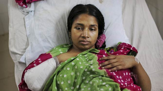 A Bangladeshi garment worker who was rescued from a building that collapsed Wednesday lays in a hospital bed with an amputated arm sustained when she was trapped inside, in Savar, near Dhaka, Bangladesh, Sunday, April 28, 2013. A fire broke out late Sunday in the wreckage of the garment factory that collapsed last week in Bangladesh killing hundreds, with smoke pouring from the piles of shattered concrete and some of the rescue efforts forced to stop.(AP Photo/Kevin Frayer)