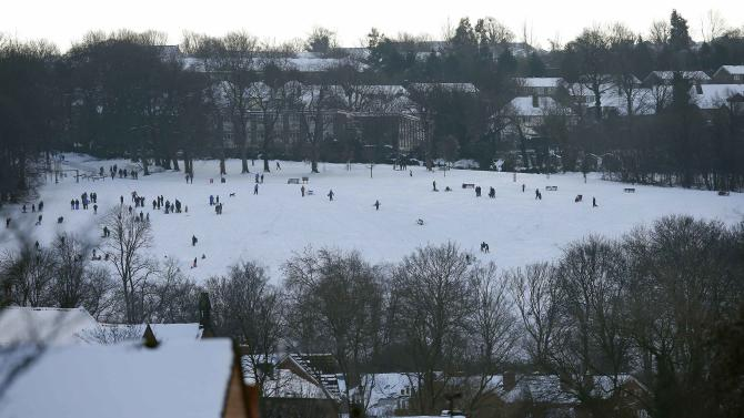 People sledge in a snow covered park in Sheffield