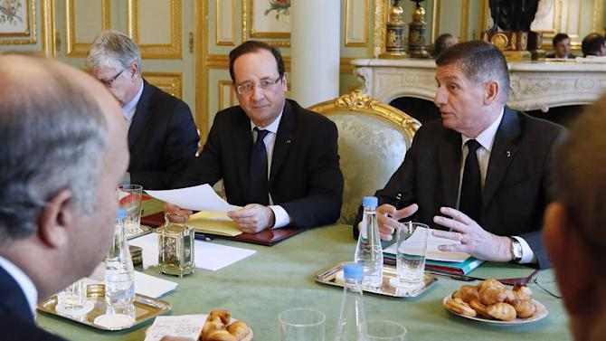 French President Francois Hollande chairs a meeting focusing on the situation in Mali next to his military chief of staff Benoit Pugat, right, and General Secretary of the Elysee presidential palace, Pierre-Rene Lemas, left partially hidden, Monday, Jan. 14, 2013, at the Elysee palace in Paris. French military forces on Monday widened their bombing campaign against Islamic extremists occupying northern Mali, launching airstrikes for the first time in central Mali to combat a new threat as the four-day-old offensive continued to grow. (AP Photo/Kenzo Tribouillard, Pool)