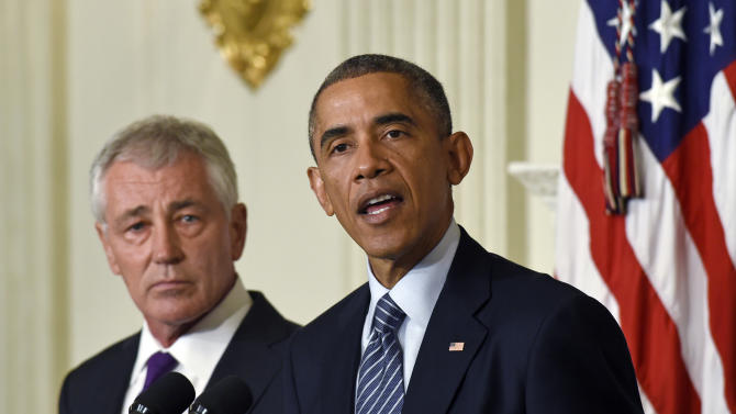 Defense Secretary Chuck Hagel, left, listens as President Barack Obama, right, talks about Hagel's resignation during an event in the State Dining Room of the White House in Washington, Monday, Nov. 24, 2014. Hagel is stepping down under pressure from Obama's Cabinet, senior administration officials said Monday, following a tenure in which he has struggled to break through the White House's insular foreign policy team. (AP Photo/Susan Walsh)
