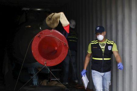 File photo of A Panamanian forensic worker carries out investigations in a container holding a MiG-21 aircraft seized from the North Korean container ship Chong Chon Gang at the Manzanillo Container Terminal in Colon city