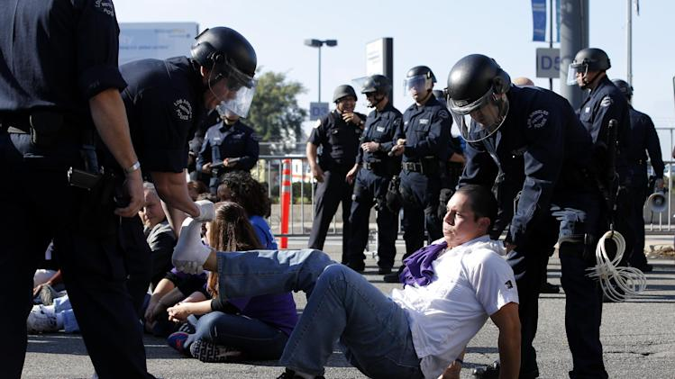 Police officers arrest Ron Gochez during a protest in Los Angeles, Wednesday, Nov. 21, 2012. Hundreds of workers at Los Angeles International Airport marched Wednesday near the entrance to Los Angeles International Airport, where Thanksgiving travelers were warned to arrive early in case of traffic snarls. (AP Photo/Jae C. Hong)