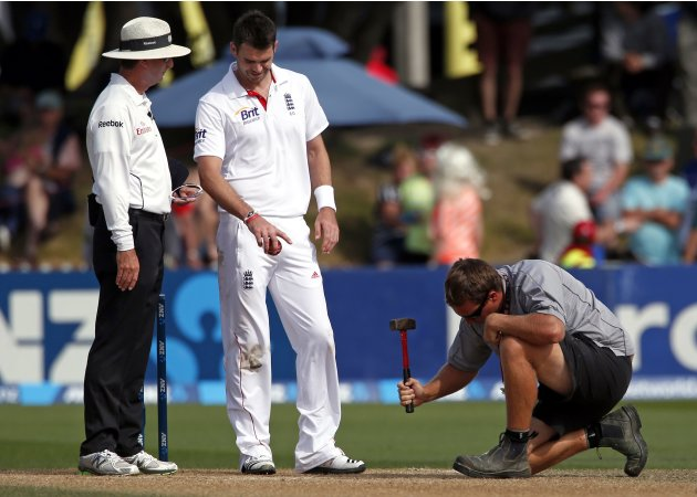England's Anderson speaks with umpire as a groundsman repairs the pitch during third day second test against New Zealand in Wellington