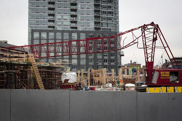 A mangled crane lies at the construction site in the Queens borough of New York where it collapsed, Wednesday, Jan. 9, 2013. The Fire Department of New York says the 200-foot crane collapsed onto a bu