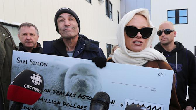 "File - In this Dec. 17, 2013 file photo, actress and animal activist Pamela Anderson, foreground right, and Sam Simon, producer of ""The Simpsons,"" second left, speak to the media after attempting to deliver a letter and a million-dollar check to end the annual commercial seal hunt to the closed office of the Canadian Sealers Association in St. John's, N.L. Fresh off a honeymoon in Israel, Anderson dispatched a letter to Benjamin Netanyahu Wednesday Jan. 23, 2014, asking the prime minister to endorse a bill banning the sale of fur. (AP Photo/The Canadian Press, Paul Daly, File)"
