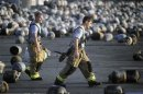 Firefighters walk among thousands of exploded propane cylinders that litter storage yard of propane plant after massive explosions overnight in the plant's yard, in Tavares