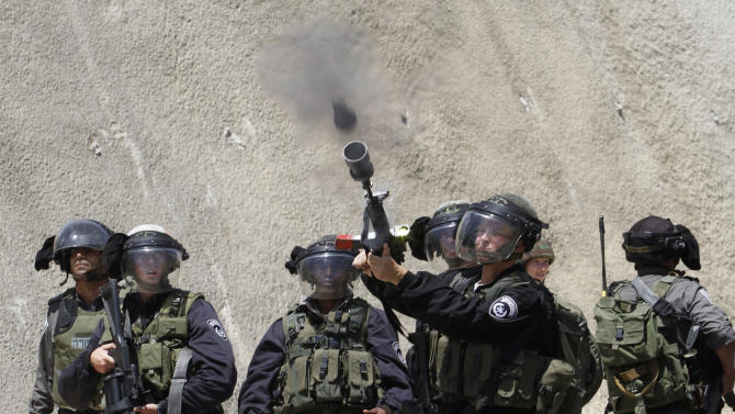 "An Israeli border policeman fires a tear gas grenade during a Palestinian rally to commemorate the 1948 creation of the Israeli state known in Arabic as ""Nakba Day"", or ""Day of the Catastrophe"" outside the West Bank town of Bethlehem, Tuesday, May 14, 2013. (AP Photo/Nasser Shiyoukhi)"