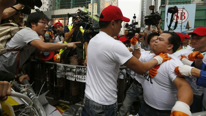 A worker representing bailiffs to clear a barricade under a court injunction at the main Nathan Road is pushed back while arguing with a pro-democracy protester at Mongkok district in Hong Kong