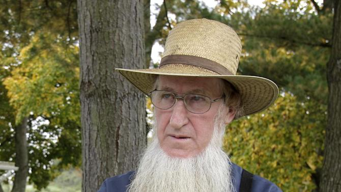 FILE- In anan Oct. 10. 2011 file photo, Sam Mullet Sr., the leader of a breakaway Amish group stands in the front yard of his Bergholz, Ohio home.  A federal judge is weighing the government's request to require the suspect in beard- and hair-cutting attacks against fellow Amish in Ohio to hire a private attorney. Federal prosecutors said in a court filing last week that Sam Mullet Sr. recently received more than $2 million from gas and oil leases on his property. ( AP Photo/File-Amy Sancetta)