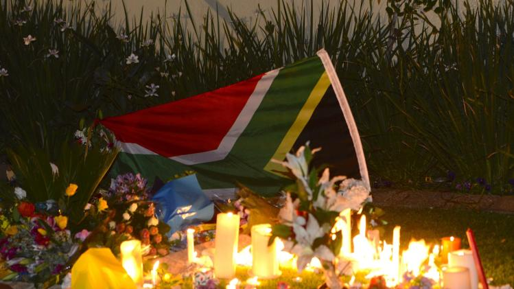 Candles burn in an impromptu shrine outside the residence of former South African President Nelson Mandela in Johannesburg