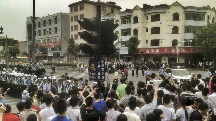 File photo of workers protesting during a strike as police stand guard at a crossroads near the factory area of Yue Yuen Industrial, in Dongguan