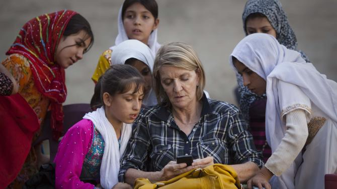 FILE - In this Saturday, Oct. 1, 2011 file photo, Associated Press Special Regional Correspondent for Afghanistan and Pakistan Kathy Gannon sits with girls at a school in Kandahar, Afghanistan. Gannon was wounded and her colleague, photographer Anja Niedringhaus, was killed on Friday, April 4, 2014 when an Afghan policeman opened fire while they were sitting in their car in eastern Afghanistan. (AP Photo/Anja Niedringhaus, File)