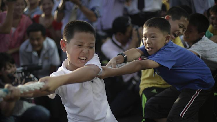 """North Korean children grimace as they challenge pro wrestlers in a tug of war game Friday, Aug. 29, 2014 in Pyongyang, North Korea. Former NFL player Bob """"The Beast"""" Sapp and a group of brawny pro wrestlers led by a Japanese politician took their oddball attempt at sports diplomacy to the streets of Pyongyang on Friday, staging a tug-war and arm wrestling competition with local children before a large and somewhat bewildered crowd of spectators. (AP Photo/Wong Maye-E)"""