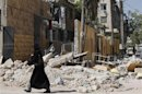 A woman passes by a school damaged by shelling in Aleppo's district of Bustan Al Qasr