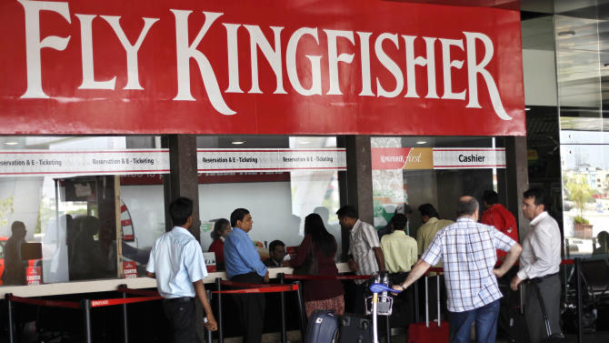 Passengers wait outside Kingfisher ticket counter at the domestic airport in Mumbai, India, Tuesday, March 20, 2012. The severely cash-strapped airlines may now face the risk of cancellation of its flying permit after the Directorate General of Civil Aviation (DGCA) expressed doubts on its ability to maintain a steady schedule with a declining number of operable aircrafts and ongoing problems with pilots leaving the company.(AP Photo/Rafiq Maqbool)