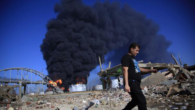 A man walks past a damaged site after a explosion as flames rise over the Amuay refinery near Punto Fijo, Venezuela, Sunday, Aug. 26, 2012. Venezuelans who live next to the country's biggest oil refinery said they smelled a strong odor of sulfur hours before a gas leak ignited in an explosion on Saturday that killed at least 39 people and injured more than 80. (AP Photo/Ariana Cubillos)