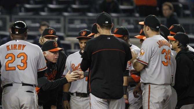 Baltimore Orioles players and coaches gather around manager Buck Showalter , second from left, as they present him with the game ball from the Orioles 7-1 win over the New York Yankees, giving Showalter his 1,000th victory, following their baseball game at Yankee Stadium in New York, Tuesday, May 1, 2012. (AP Photo/Kathy Willens)