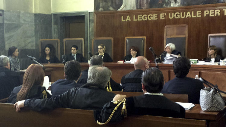 "Karima el-Mahroug, from Morocco, the woman at the center of a sex scandal involving former Italian Premier Silvio Berlusconi, is seen sitting in the witness stand at left speaking into a microphone as she testifies for the first time in the trial of three Berlusconi aides charged with recruiting her and other women for prostitution, in Milan's courthouse, Italy, Friday, May 17, 2013. El-Mahroug, known by the nickname Ruby Heart Stealer, has made carefully orchestrated statements to the media since the scandal broke but has never publicly given sworn testimony. Both she and Berlusconi deny having had sex. Prosecutors in Berlusconi's separate trial on charges of paying for sex with a minor and trying to cover it up say her testimony is unreliable and are relying on her sworn statements. Writing above judges reads in Italian ""The law is equal for all.""(AP Photo/Luca Bruno)"