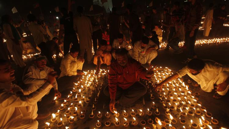 Supporters of Imran Khan light earthen lamps during a peace vigil in Karachi