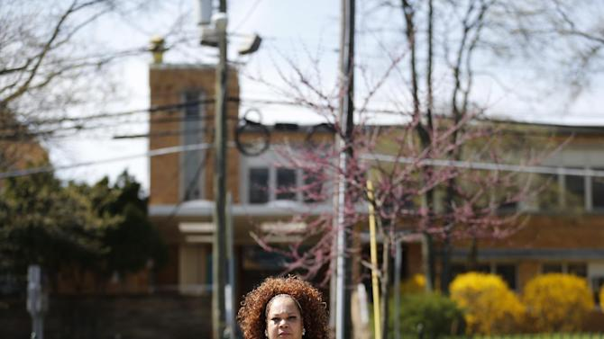 In this Wednesday, April 22, 2015 photo, Shalga Hightower, mother of  Iofemi Hightower, college student slain in 2007, poses for The Associated Press across the street from the school where the murder happened in Newark, N.J. In the seven-plus years since her college-bound daughter's brutal slaying along with two friends in a case that became a national symbol of urban gun violence, Hightower has been on a mission. It started with a resolve to attend every court hearing involving the six men and boys eventually convicted for the crime, an odyssey that cost her her job and left her family temporarily homeless. Now, a documentary project is aiming to chronicle her struggles and her efforts on behalf of families of crime victims who are too often left to fend for themselves. (AP Photo/Julio Cortez)