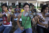 "In this Dec. 11, 2012 photo, Ada Rios, center, plays a violin made of recycled materials during a practice session with ""The Orchestra of Instruments Recycled From Cateura"" in Cateura, a vast landfill outside Paraguay's capital of Asuncion, Paraguay. ""The orchestra has given a new meaning to my life, because in Cateura, unfortunately, many young people don't have opportunities to study, because they have to work or they're addicted to alcohol and drugs,"" Rios said. (AP Photo/Jorge Saenz)"