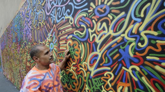 """In this Friday, July 27, 2012 photo, graffiti artist Angel """"LA II"""" Ortiz, 45, poses for photos with one of his creations, in a schoolyard on New York's Lower East Side. A number of New York's graffiti artists of the 1970s and '80s still have the urge to tag. (AP Photo/Richard Drew)"""