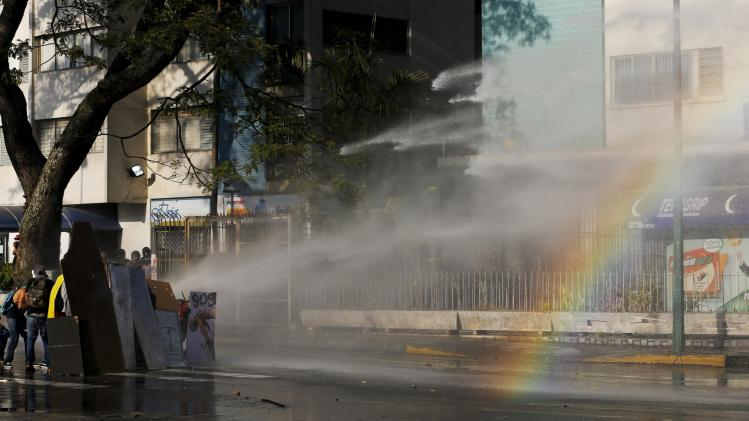Anti-government protesters are hit by the water cannon during clashes with police at Altamira square in Caracas