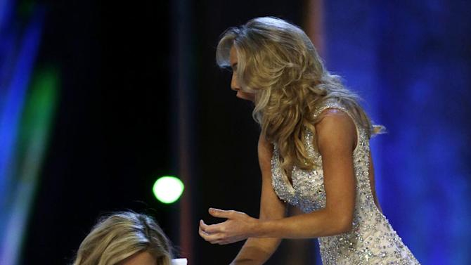 Miss New York Kira Kazantsev, left, celebrates after she was named Miss America 2015 as she holds hands with Miss Virginia Courtney Paige Garrett during the Miss America 2015 pageant, Sunday, Sept. 14, 2014, in Atlantic City, N.J. (AP Photo/Julio Cortez)