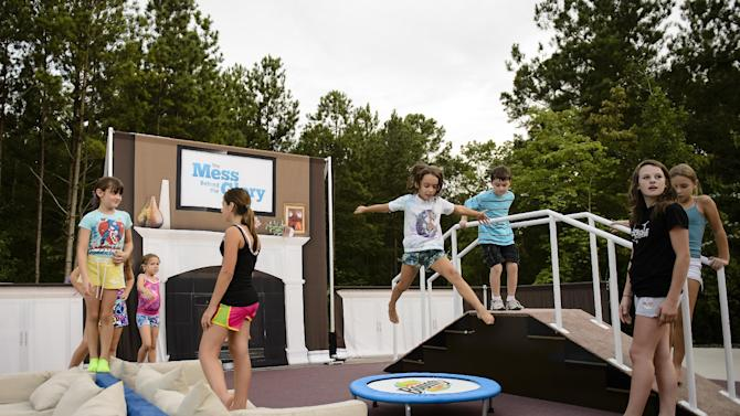 COMMERCIAL IMAGE - In this photograph released by Bounty on Tuesday, August 7, 2012, Megan Sims and her daughters, Delaney (yellow shorts) and Cidella (jumping), celebrate with their friends during Bounty's Mess Behind The Glory Contest Viewing Party in Monroe, Ga. (Paul Abell/AP Images for Bounty)