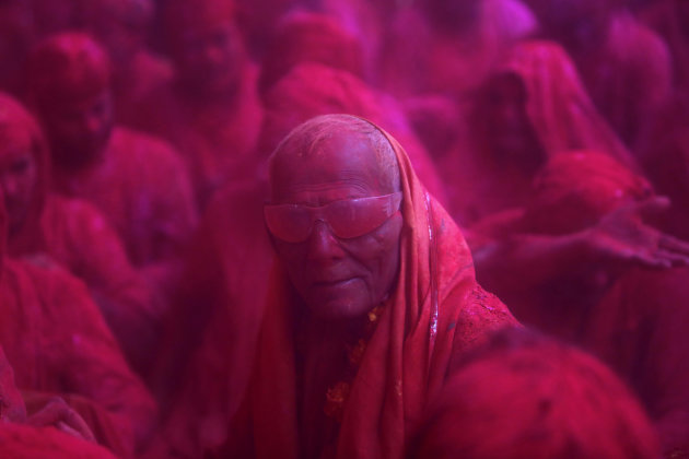 "A Hindu devotee looks on in a cloud of coloured powder inside a temple during ""Lathmar Holi"" at the village of Barsana"