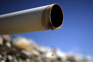 A dry pipe drips water on Gless Ranch in Kern County